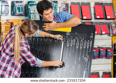 Young salesman with female customer examining wrench using board in hardware store - stock photo