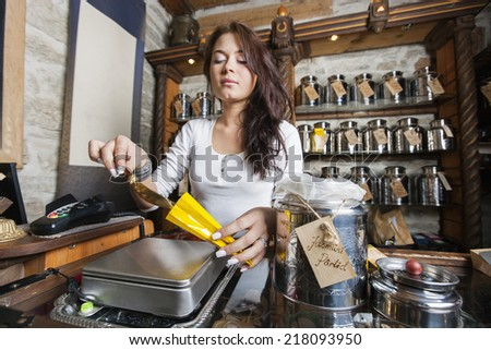 Young salesperson scooping ingredient into paper bag at tea store - stock photo