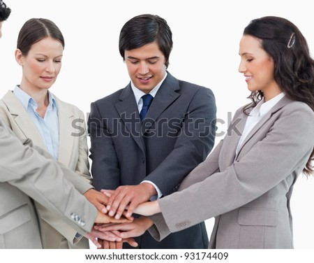 Young salesteam putting hands together against a white background