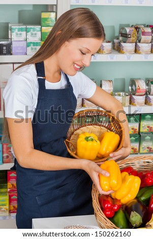 Young saleswoman choosing bellpeppers in grocery store - stock photo
