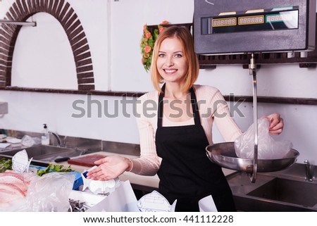 young saleswoman weighing fresh fish in shop