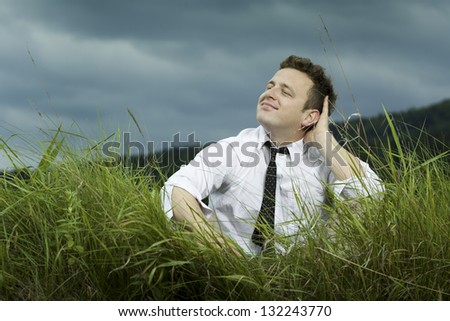 Young satisfied businessman sitting on the meadow, dressed in a shirt unbuttoned, thinking. Forest in the background. - stock photo