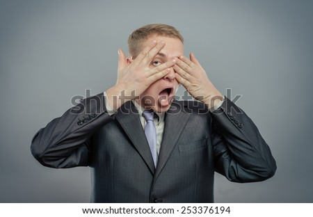young scared adult with hand covering eyes  - stock photo