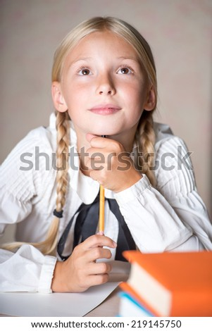 Young school girl dreaming while lesson - stock photo