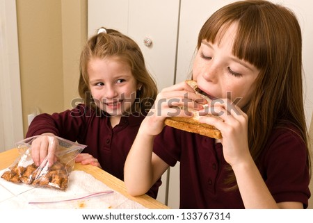 Young school girl eating lunch while a younger girls sneaks a pretzel - stock photo