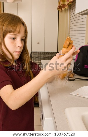 Young school girl preparing her lunch - stock photo