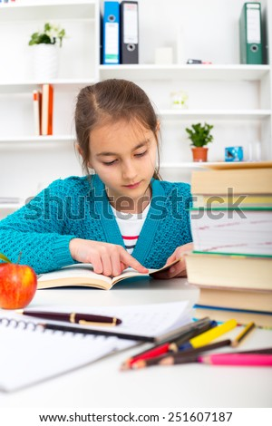 Young school girl reading a book.