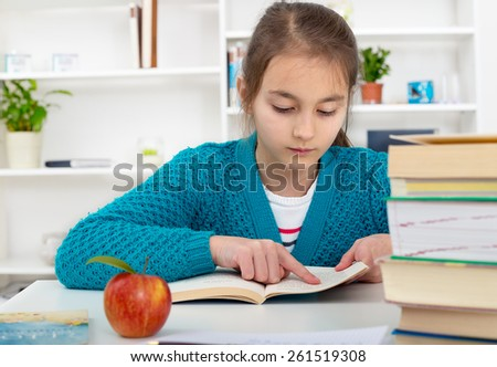 Young school girl reading a book - stock photo