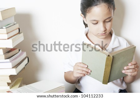 Young school girl reading a book whilst sitting down next to piles of books at home.
