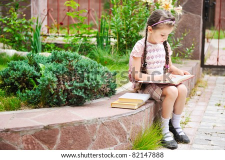 Young school girl with pink backpack ready for school sits reading the book - stock photo