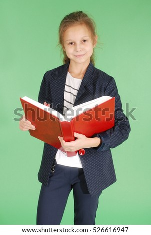 Young school girl with red book isolated on green