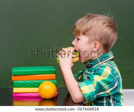 Young schoolboy eating hamburger - stock photo