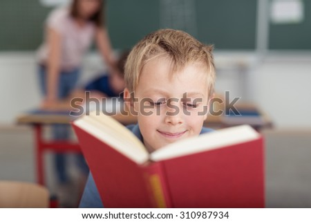 Young schoolboy reading from a large red hardcover textbook with a smile as he sits at his desk in a classroom with his teacher visible in the background - stock photo