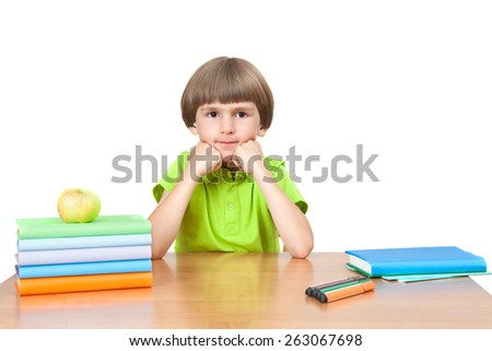 Young schoolboy sits at table with books and apple - stock photo