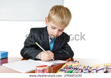 Young schoolboy with desk and blackboard on white background. writing - stock photo