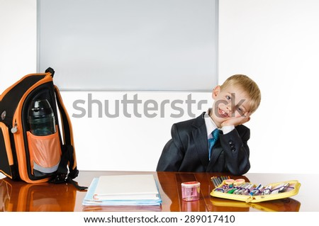 Young schoolboy with desk satchel and blackboard on white background. thinking - stock photo