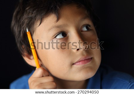 Young schoolboy with pencil - with chiaroscuro lighting - shallow depth of field