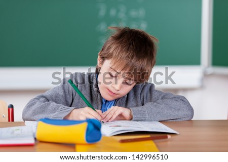 Young schoolboy writing in his exercise book in the classroom - stock photo