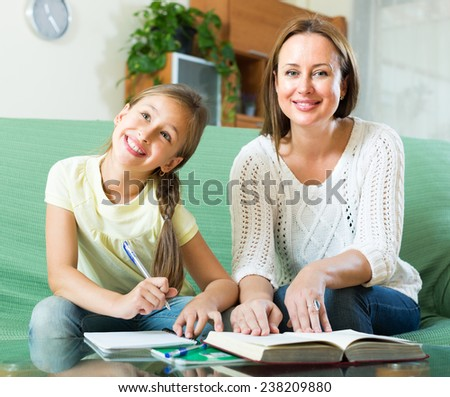 young schoolgirl and mother together doing homework in home - stock photo