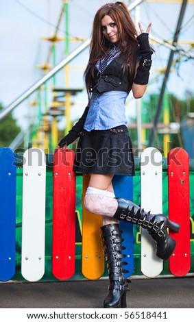 Young schoolgirl in amusement park. - stock photo