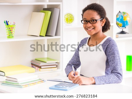 Young schoolgirl  in glasses sitting at the table and writing homework on colorful background. - stock photo