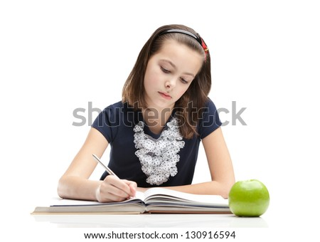 Young schoolgirl is doing her homework, isolated, white background - stock photo