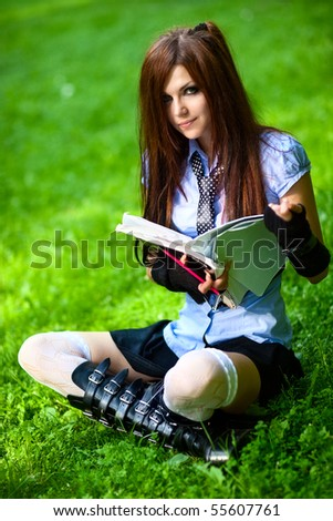 Young schoolgirl reading exercise book in park. - stock photo