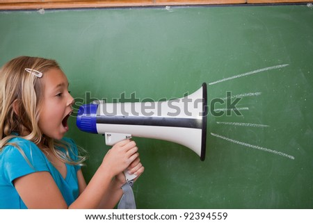 Young schoolgirl screaming through a megaphone in front of blackboard - stock photo