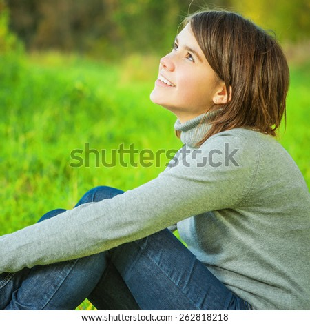 Young schoolgirl sits on autumn to clearing. - stock photo