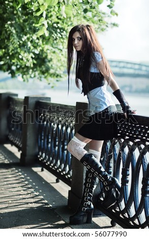 Young schoolgirl standing at the railing. - stock photo