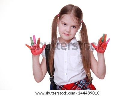 young schoolgirl wearing white blouse and red skirt cell with funny two tails and school bag/Portrait of charming pupil has hands in colorful finger paints - stock photo