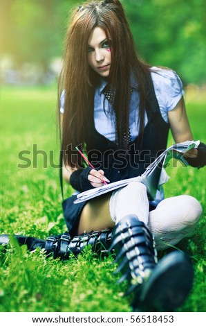 Young schoolgirl with exercise book in park. - stock photo