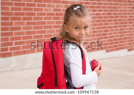 Young Schoolgirl with red backpack standing against brick school wall, holding an apple - stock photo