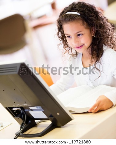 Young schoolgirl working on a computer at school - stock photo