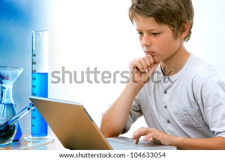 Young science student studying with laptop and lab equipment.