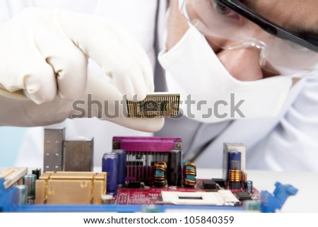 Young scientist installing a microchip computer on the motherboard