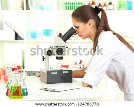 Young scientist looking into  microscope in  laboratory