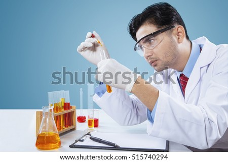 Young scientist observes his research by using chemical liquid in the laboratory