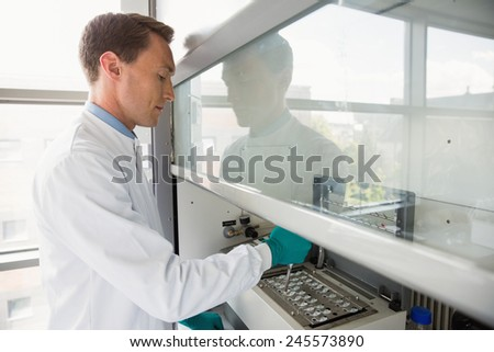 Young scientist using a pipette in chamber at the laboratory - stock photo