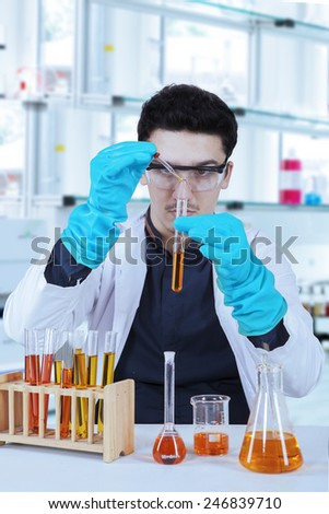 Young scientist with lab coat, gloves, and protective glasses doing experiment in laboratory - stock photo