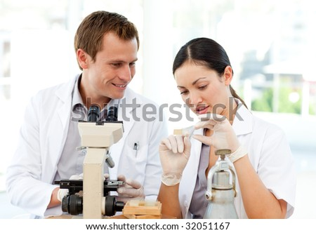 Young scientists studying a slide under a microscope