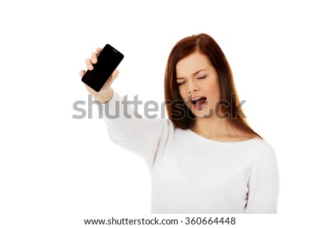 Young screaming woman shows broken touch screen mobile phone - stock photo