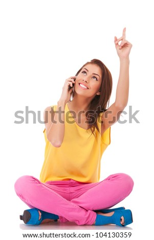 young seated casual woman talking on the phone, pointing and looking up to something
