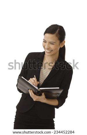 Young secretary making notes to personal organizer, smiling happy. - stock photo
