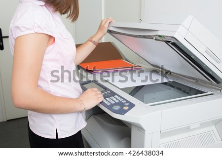 Young secretary using a copy machine at office with red shirt - stock photo