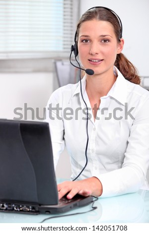 Young secretary with headphones and microphone - stock photo