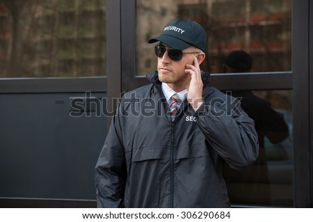 Young Security Guard Standing In Front Of The Glass Door Entrance - stock photo