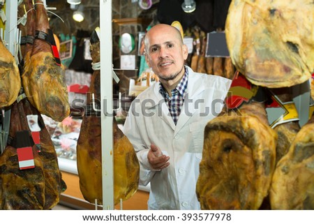 young seller with wurst and jamon in meat store counter