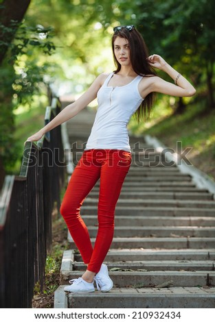 Young sensual beautiful brunette woman having fun on the stairs in the summer park