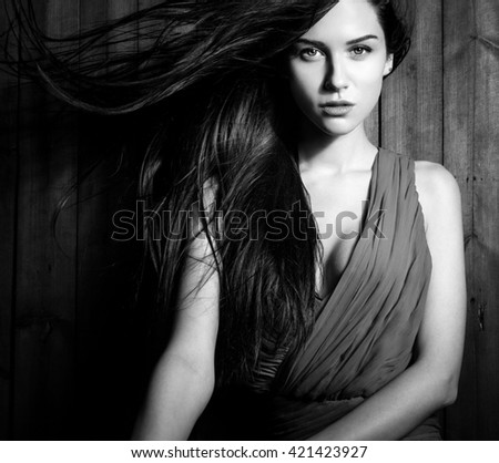 Young sensual & beauty woman in casual clothes pose on grunge wooden background. Black-white fashion photo.